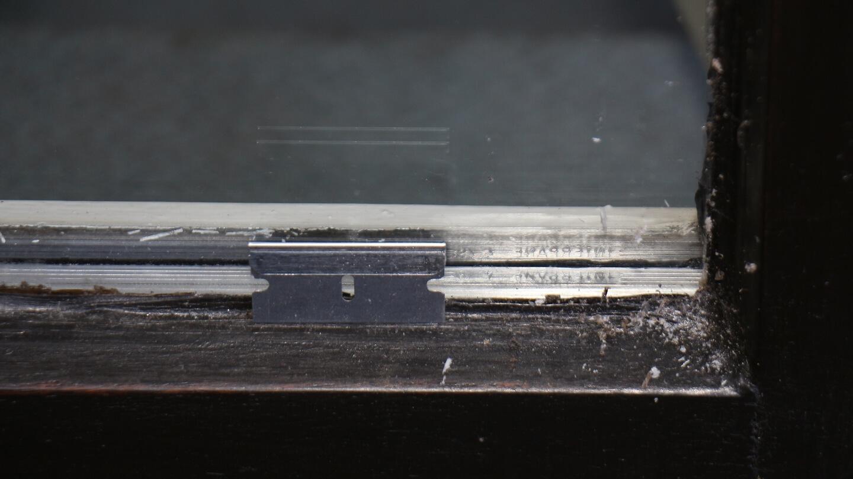 Mit der Schaberklinge anhaftenden Schmutz entfernen, dann Spiegelfolie aufkleben