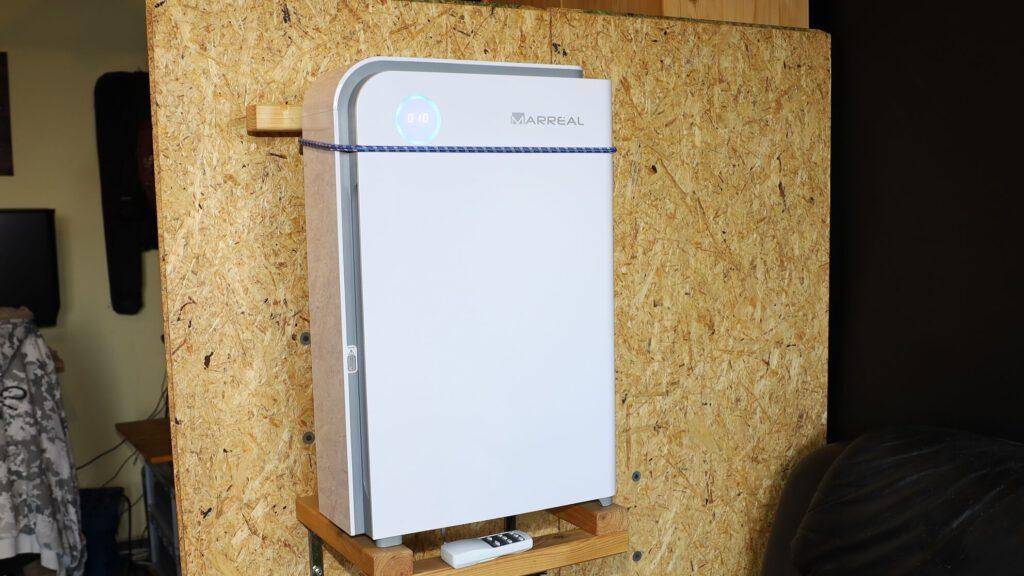 Dieser HEPA Luftreiniger steht auf halber Raumhöhe an einem Raumtrenner aus Holz