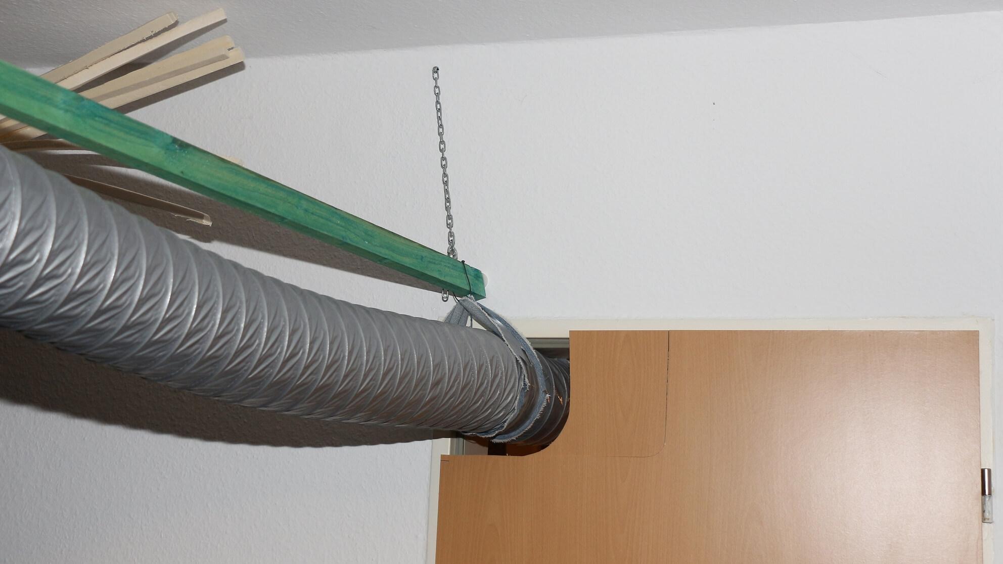 Von der Holzleiste hängt dieser Luftschlauch runter und läuft durch die Tür-Auslassung